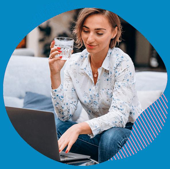 mujer-bebiendo-agua-frente-a-un-ordenador